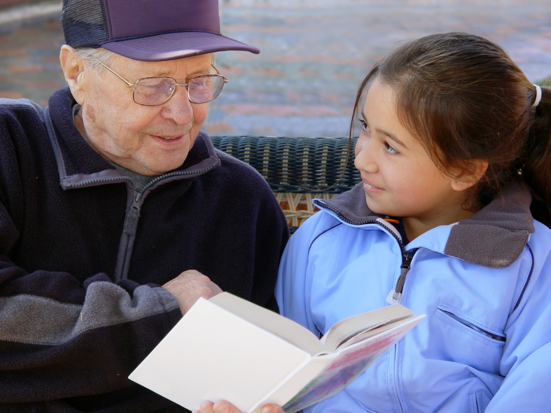 A senior reading a book to a child