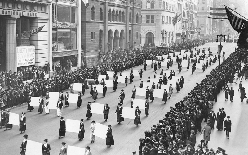 Suffragists parade down Fifth Avenue, 1917. Advocates march in October 1917, displaying placards containing the signatures of more than one million New York women demanding the vote.