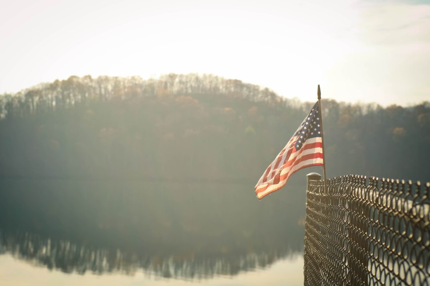 American flag hanging over lake.