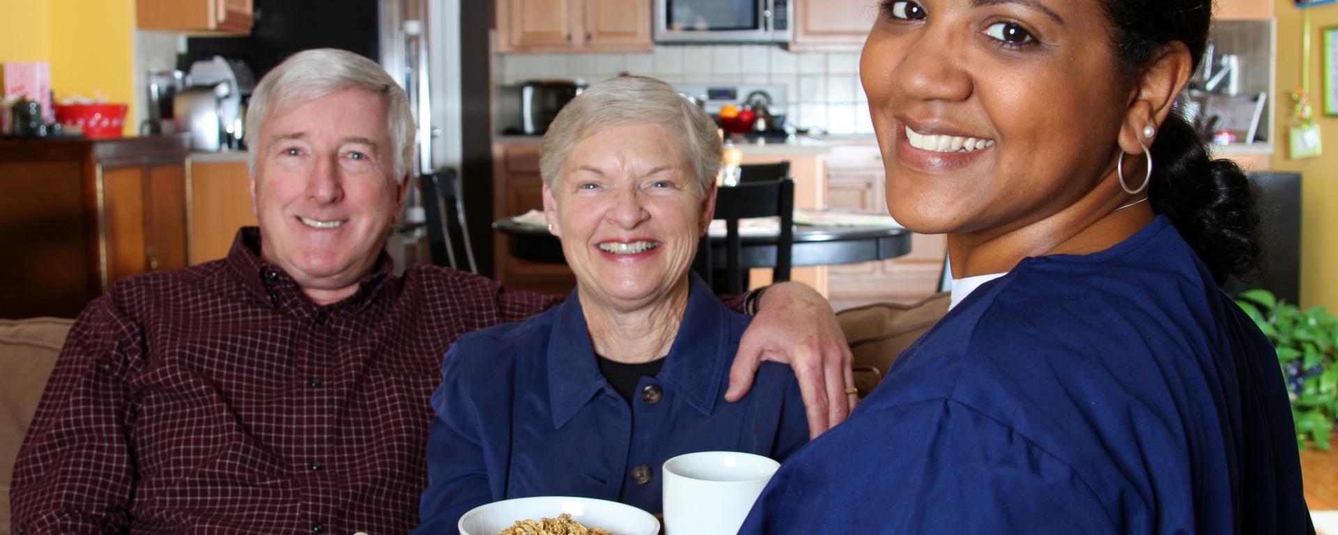 Caregiver bringing a tray of food to seniors.
