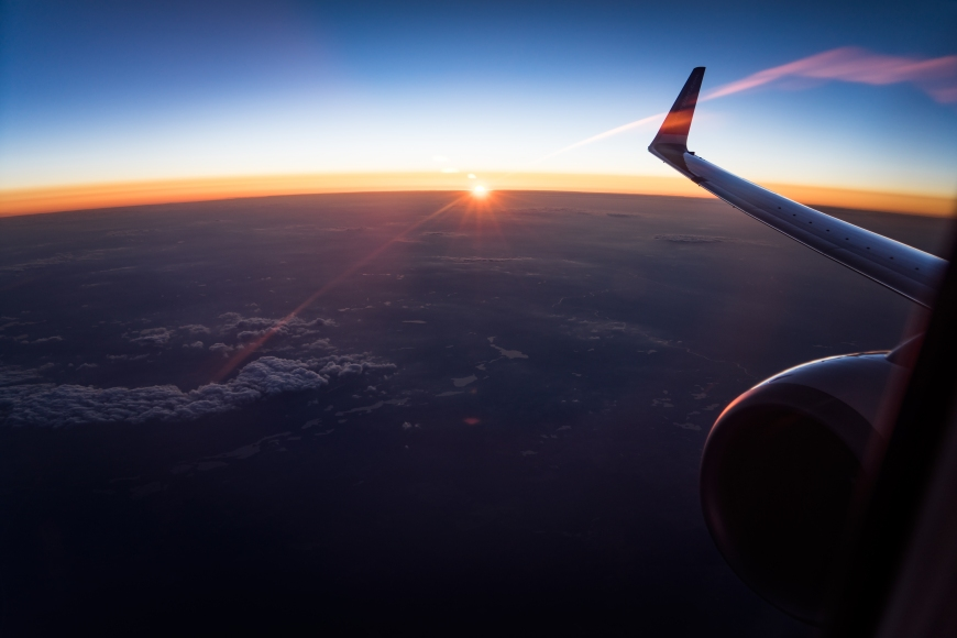 Sun setting over horizon viewed from airplane.