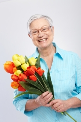 Senior smiling with flowers