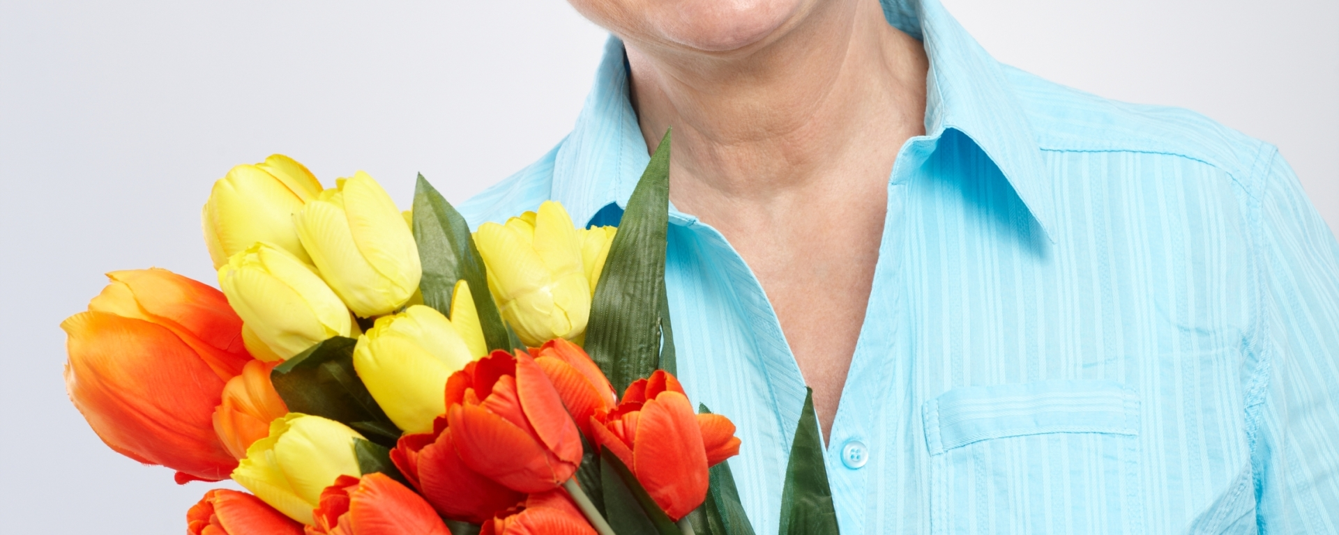 Senior woman smiling and holding a bouquet of tulips.