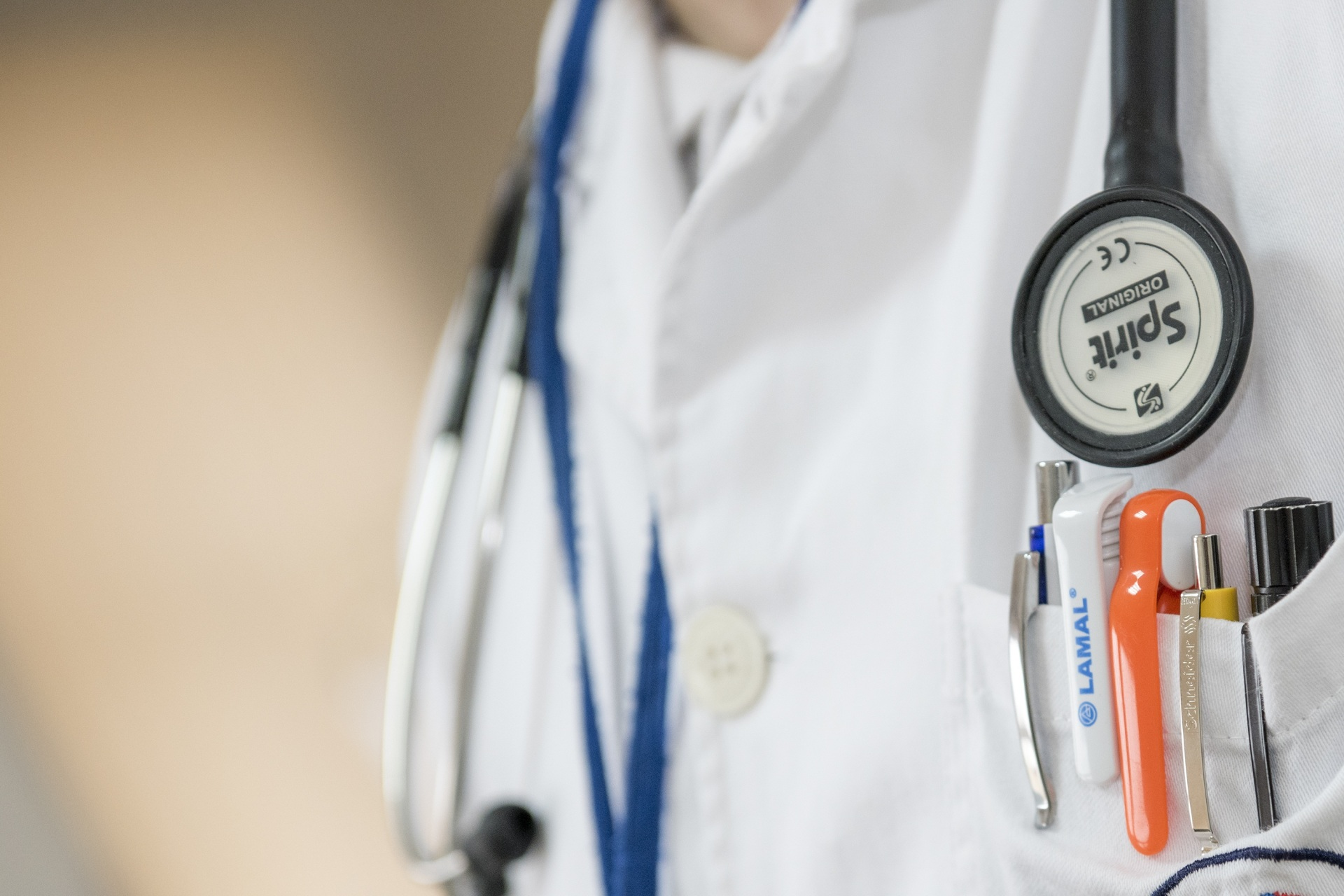Closeup of doctor's white coat with pens and stethoscope.