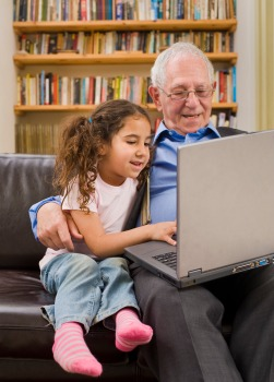 Grandparent and granddaughter with laptop computer
