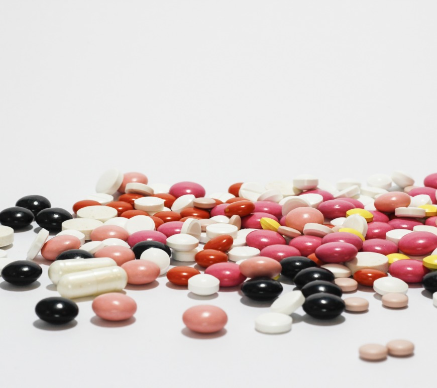 Pills spread out on a white surface.