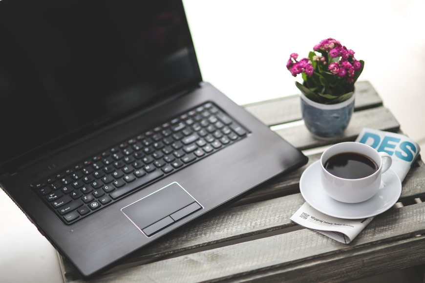 Laptop with coffee cup and jar of flowers.