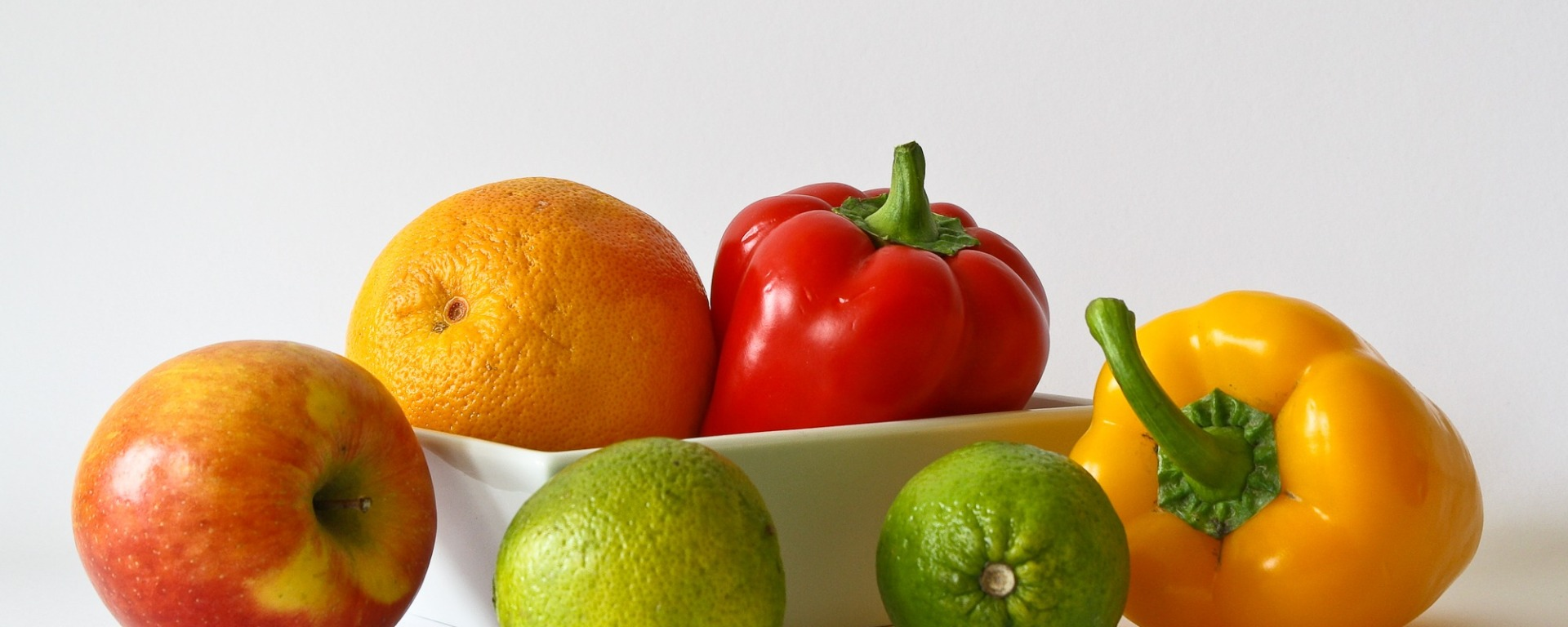 Bowl with peppers, limes, an apple, and an orange.