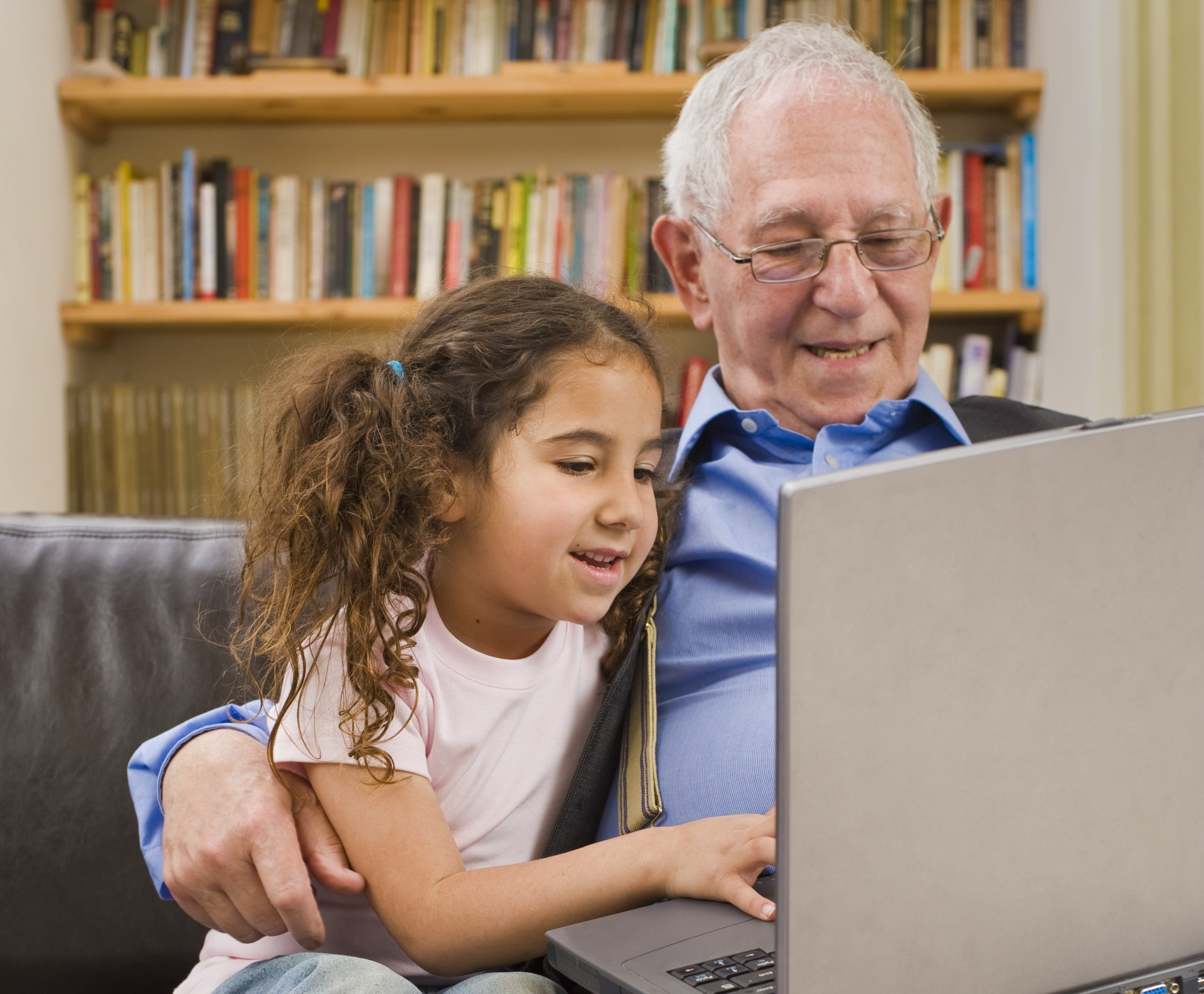 Grandfather and granddaughter with laptop computer at home