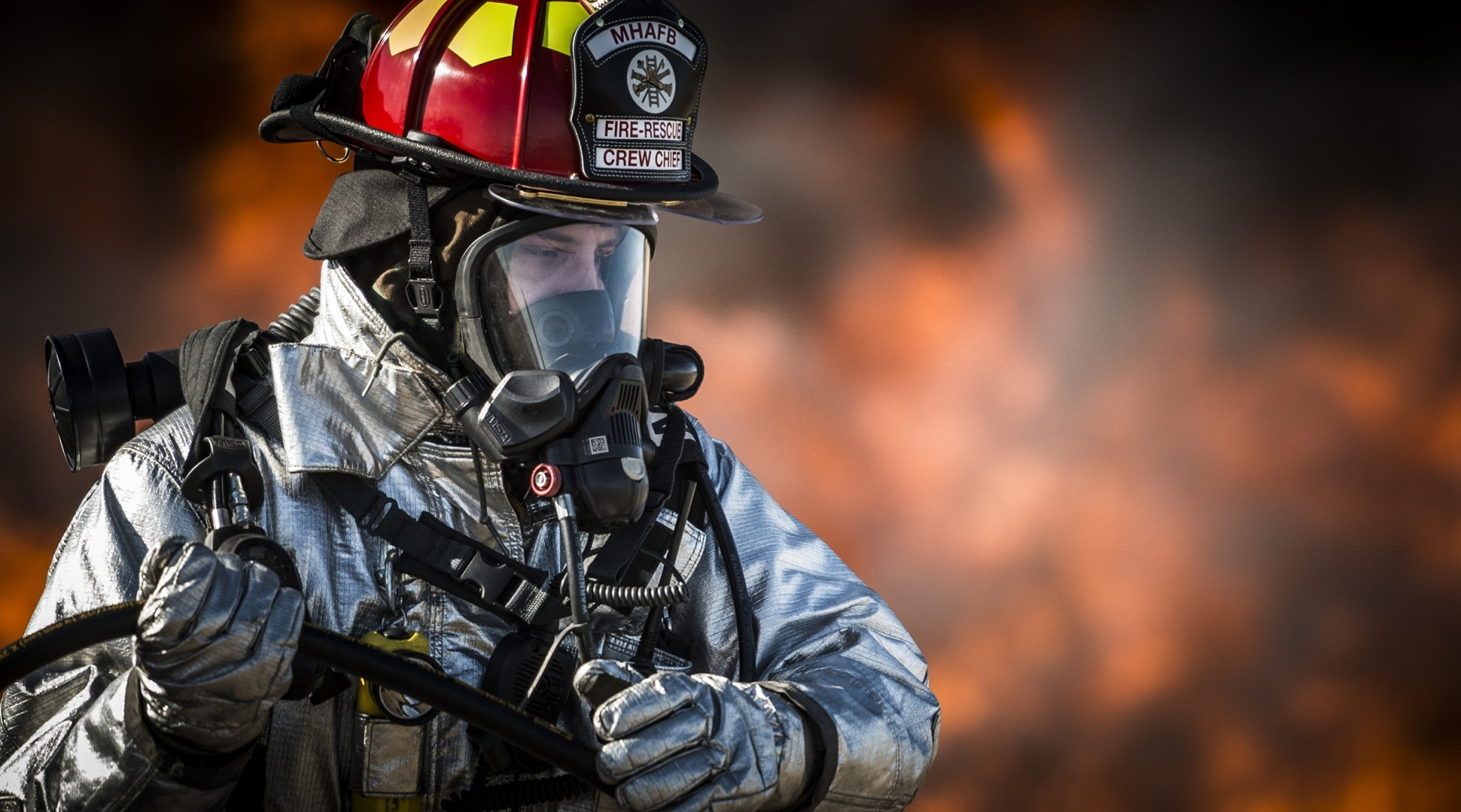 Firefighter wearing helmet and mask.