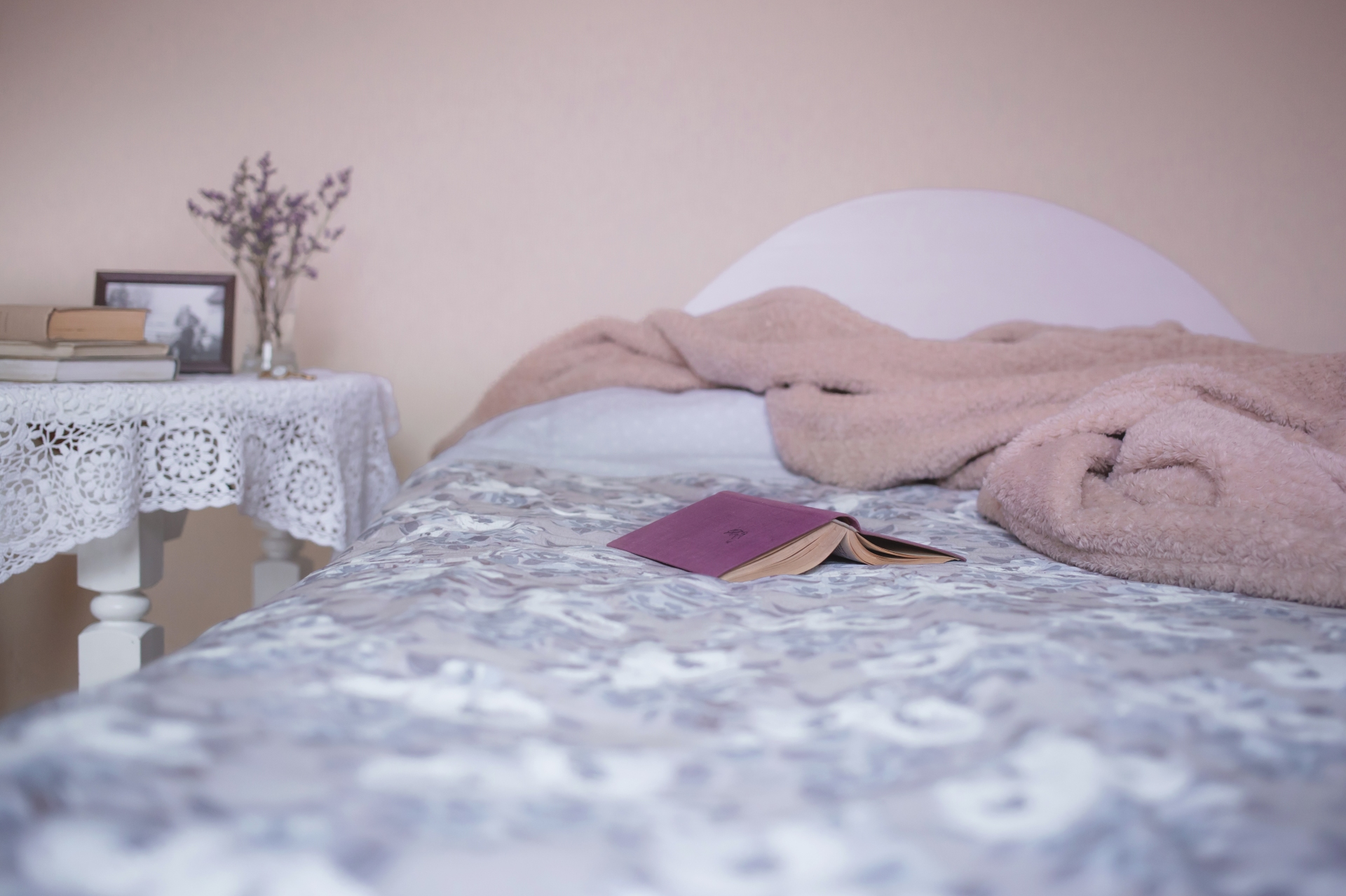 A bed made with blankets and a book lying on it.