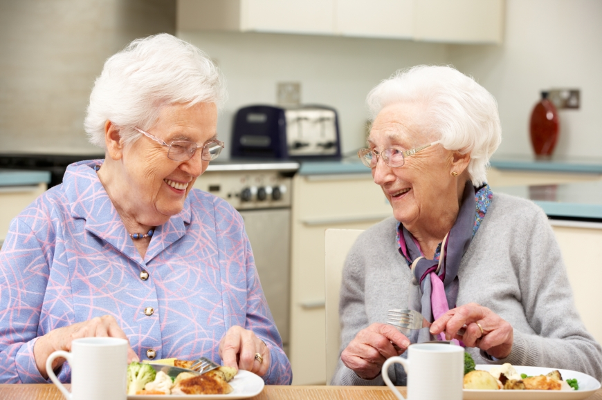 Two women eating and smiling at each other.