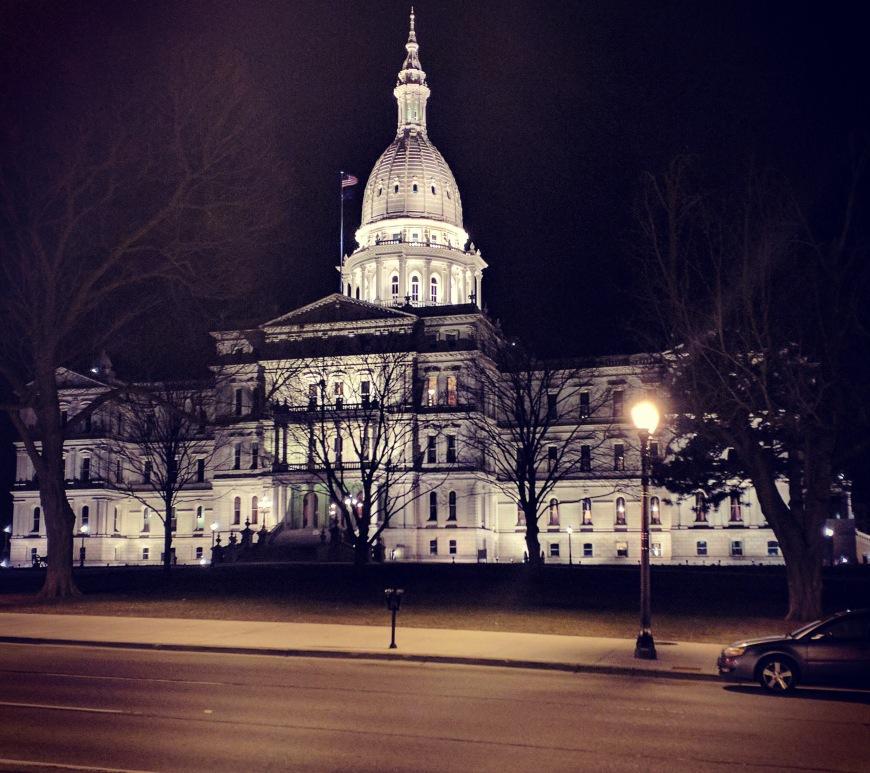 Exterior view of the Michigan Capitol Building illuminated at night.