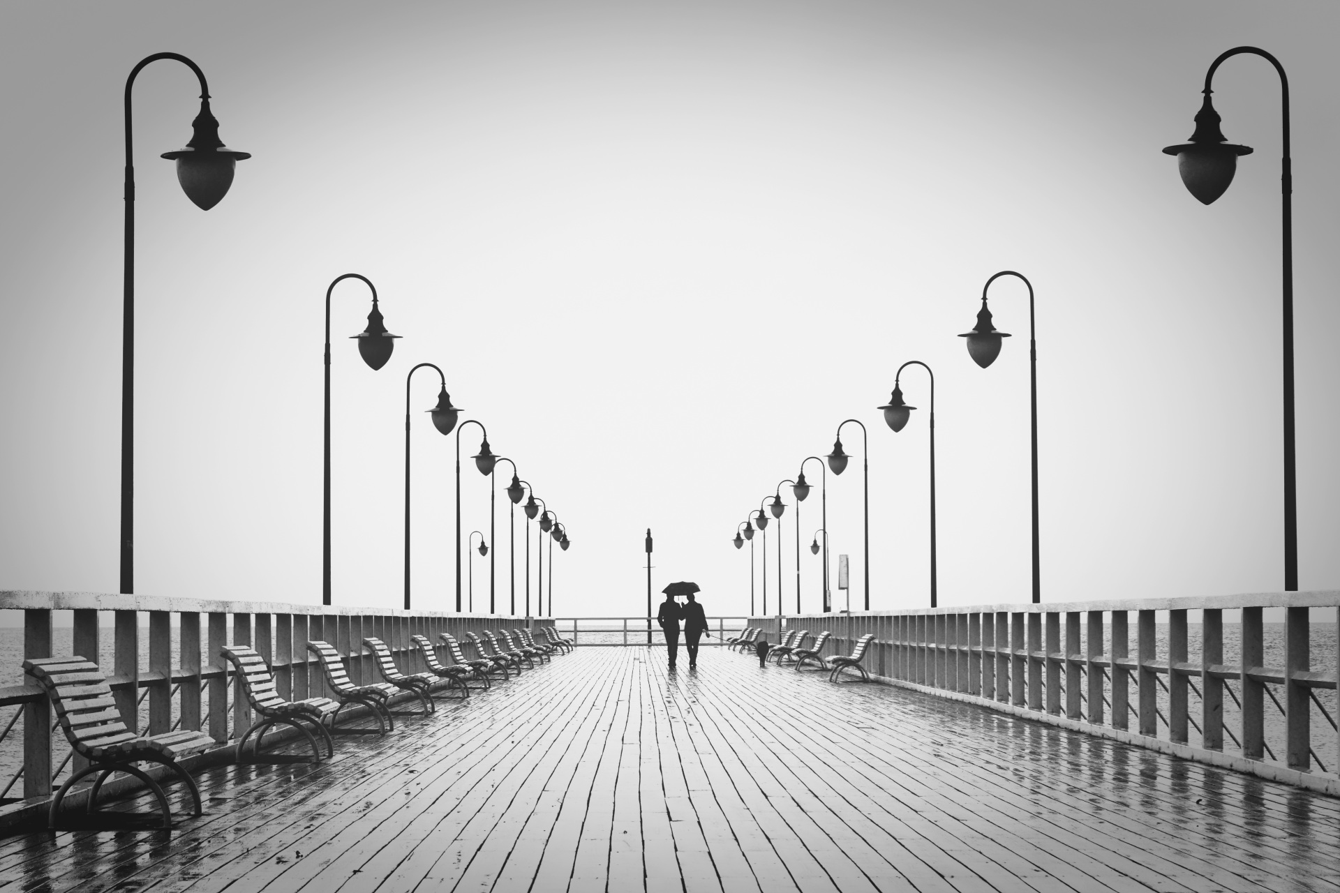 Two people walking on a pier in the rain.