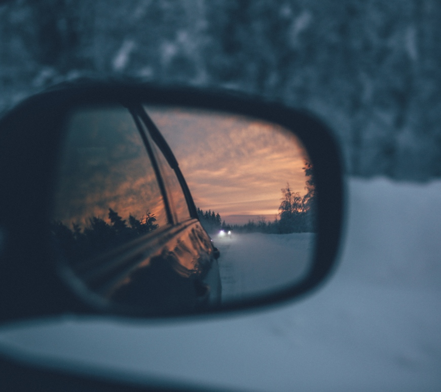 Car mirror reflecting a sunset.