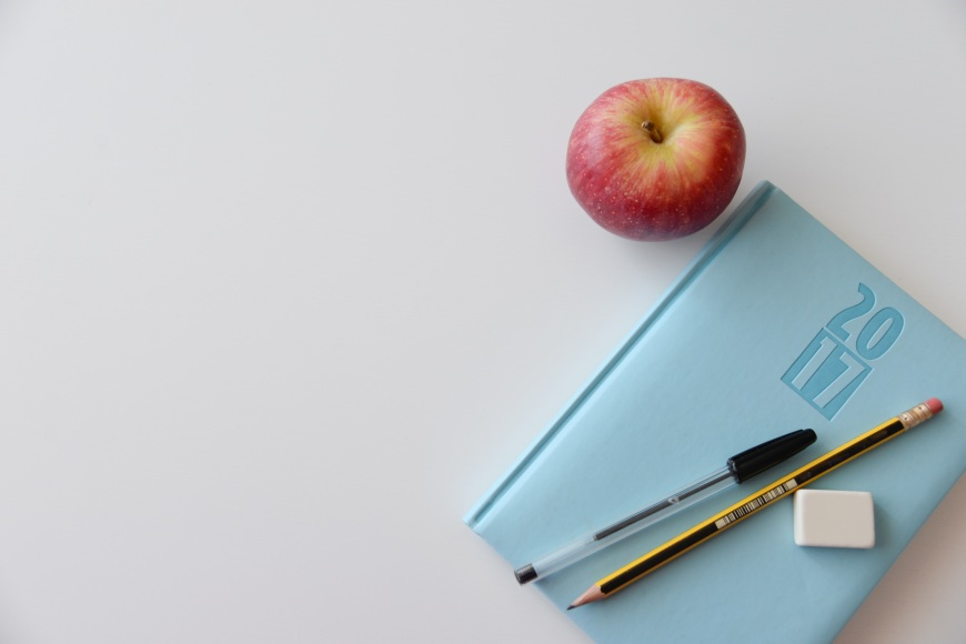 A pen and pencil sit on top of a blue notebook with 2017 embossed on the front. A red apple is next to the notebook.