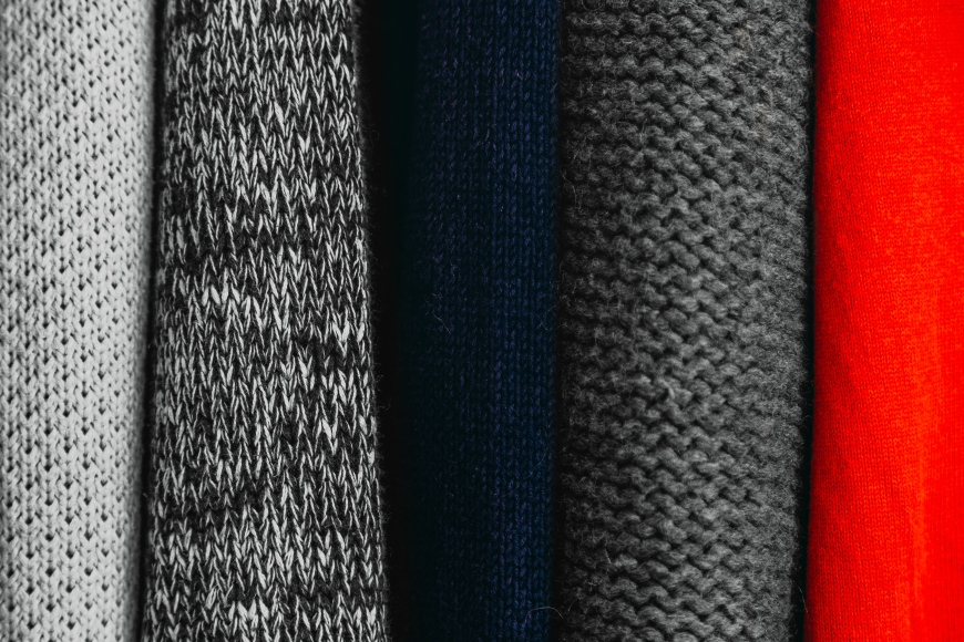 Gray, blue, and red fabrics in a stack.