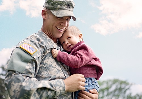 A man in a U.S. military uniform smiles while holding a toddler.