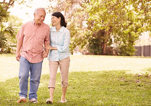 A senior couple smile and hold hands while walking outdoors.