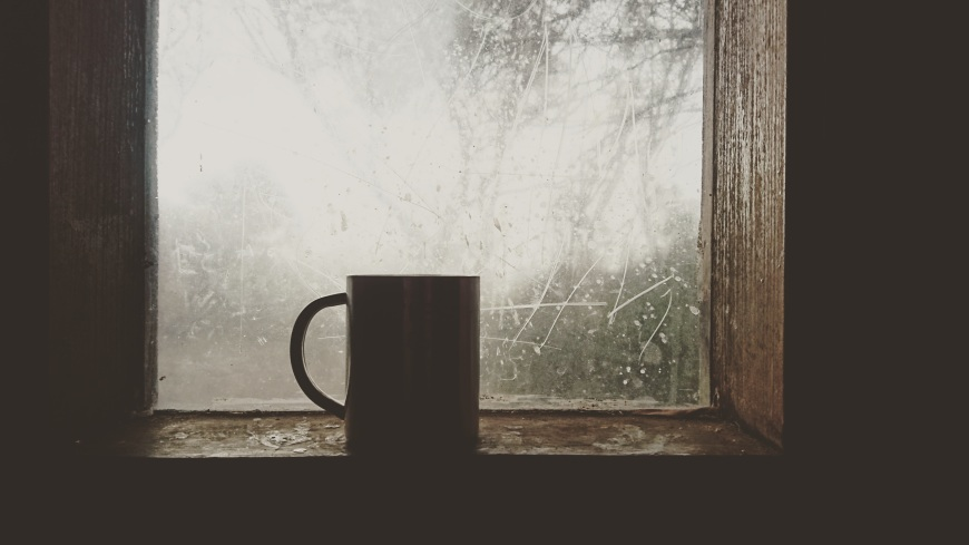 A coffee mug sits on a frosty window sill.