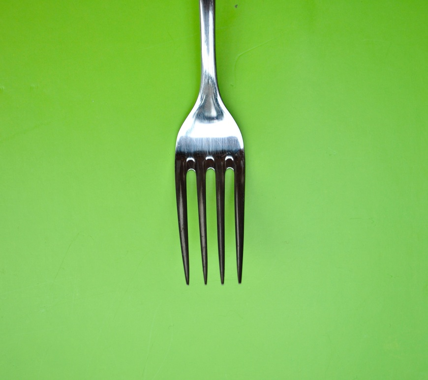 Metal fork on a green background.