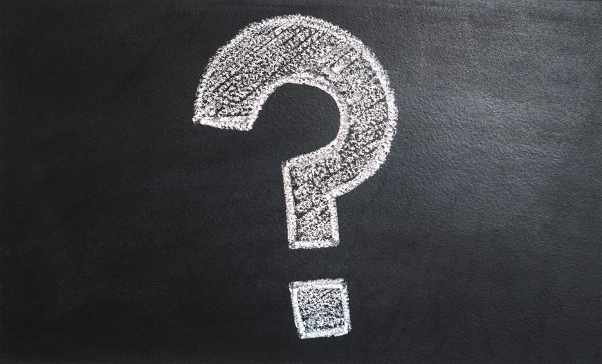 A question mark drawn in white chalk on a blackboard.