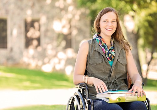 A woman in a wheelchair smiles at the camera while holding books in her lap.