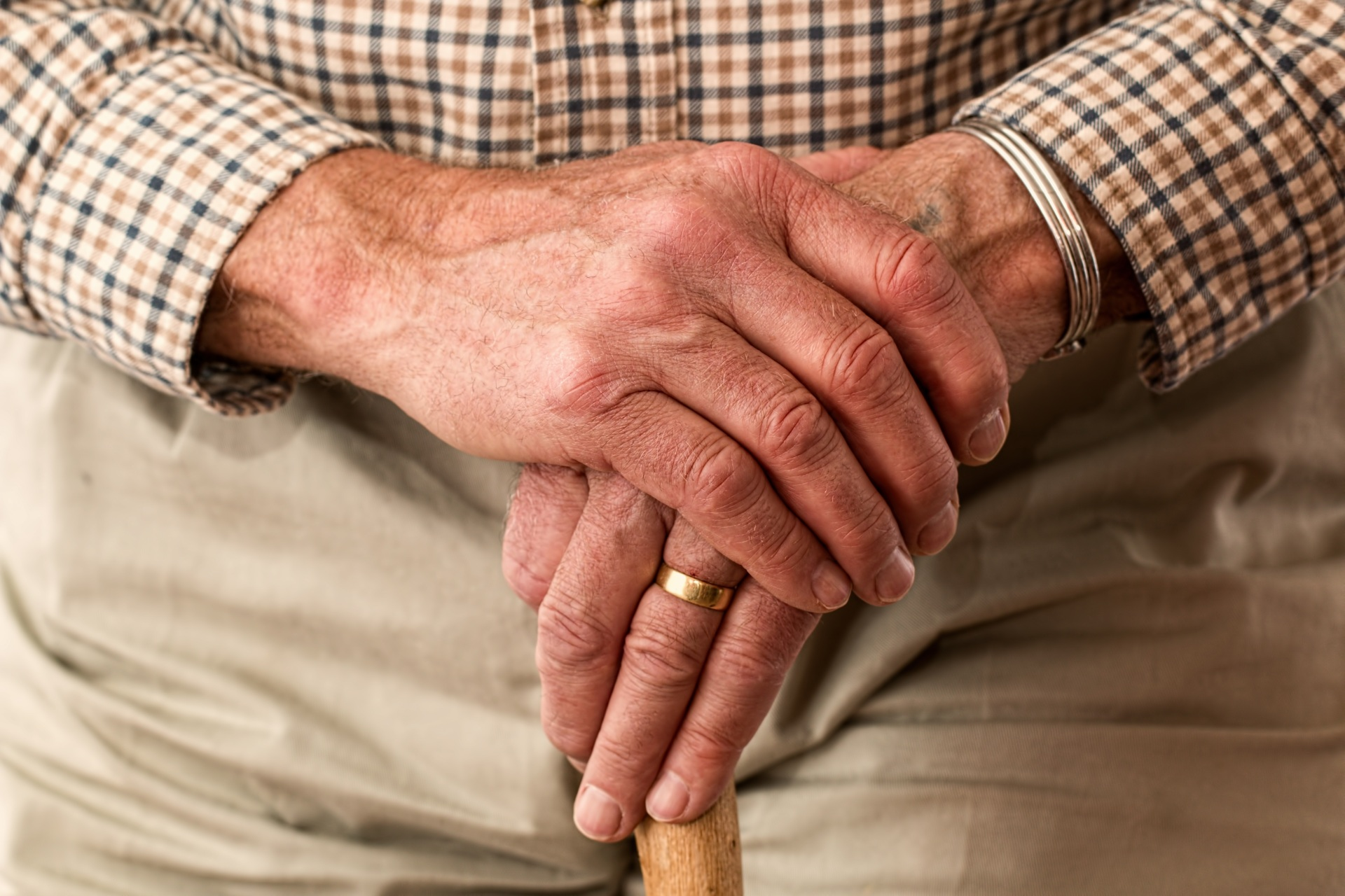 An elderly man's hands rest on top of a wooden cane.