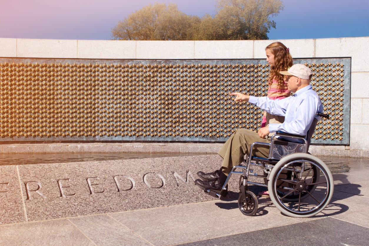 A man in a wheelchair walks with a young girl next to a war memorial.