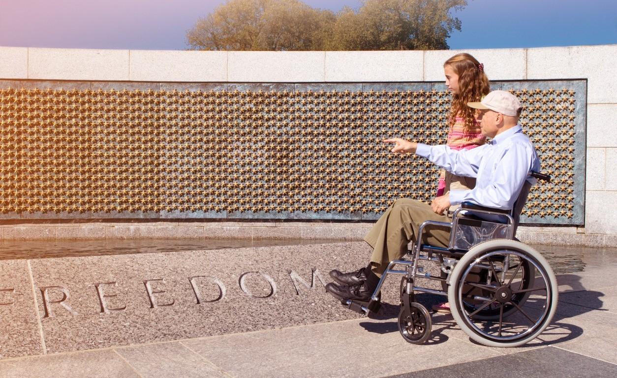 A man in a wheelchair walks with a young girl next to a war memorial.
