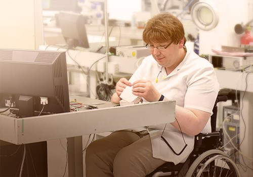 A woman in a wheelchair works at a computer station.