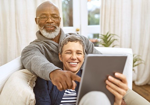 A man and woman sitting on a couch smile while using a tablet together.