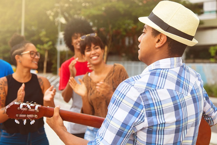 A man wearing a fedora plays guitar for a happy group of people.
