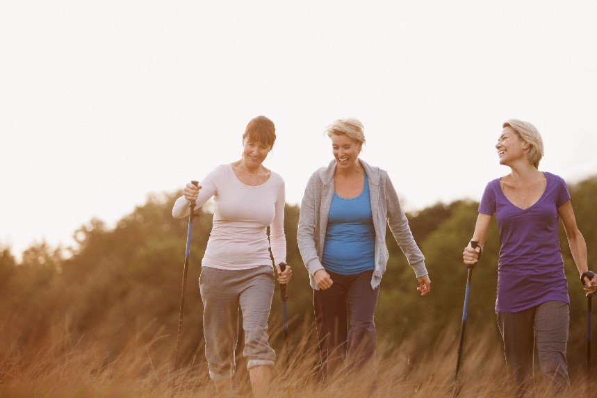Three women smile while walking in a field together.