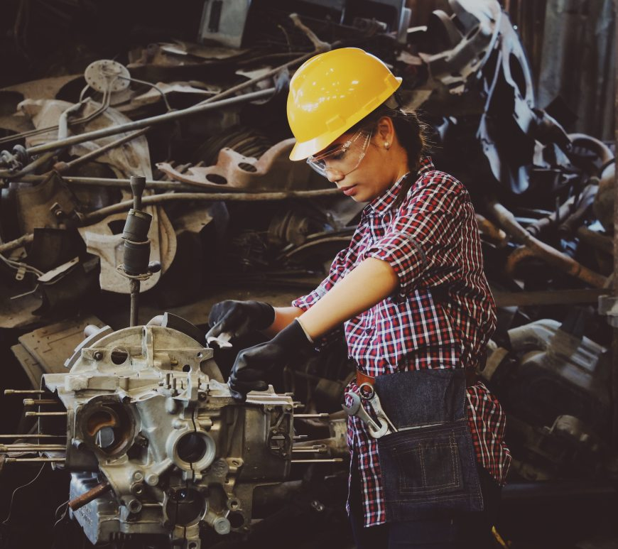 A woman wearing a hard hat works in a factory.