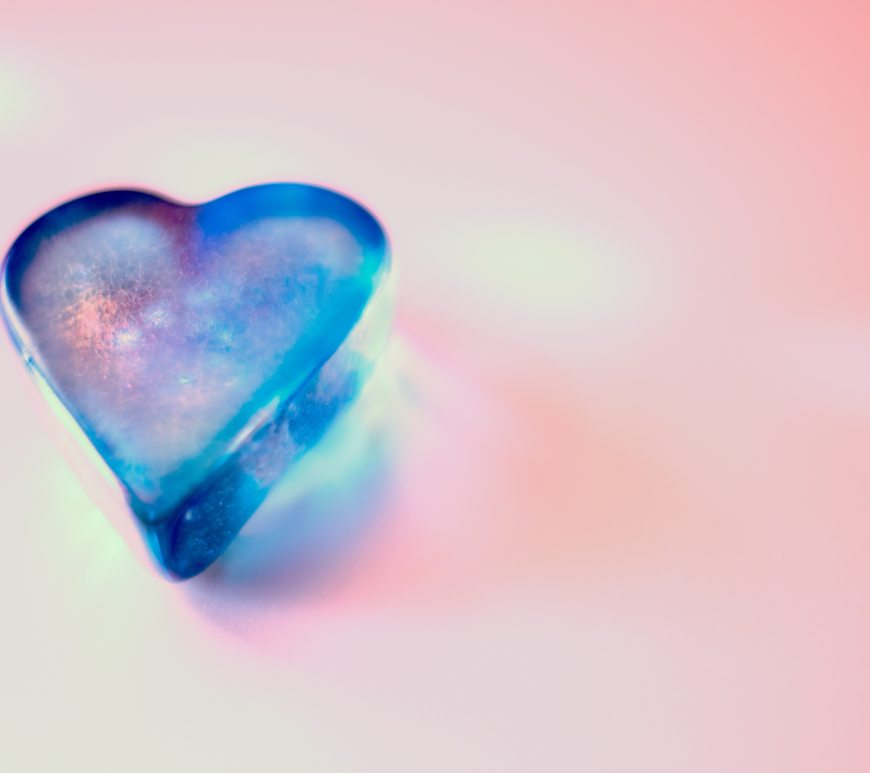 A blue frosted glass heart on a light pink background.
